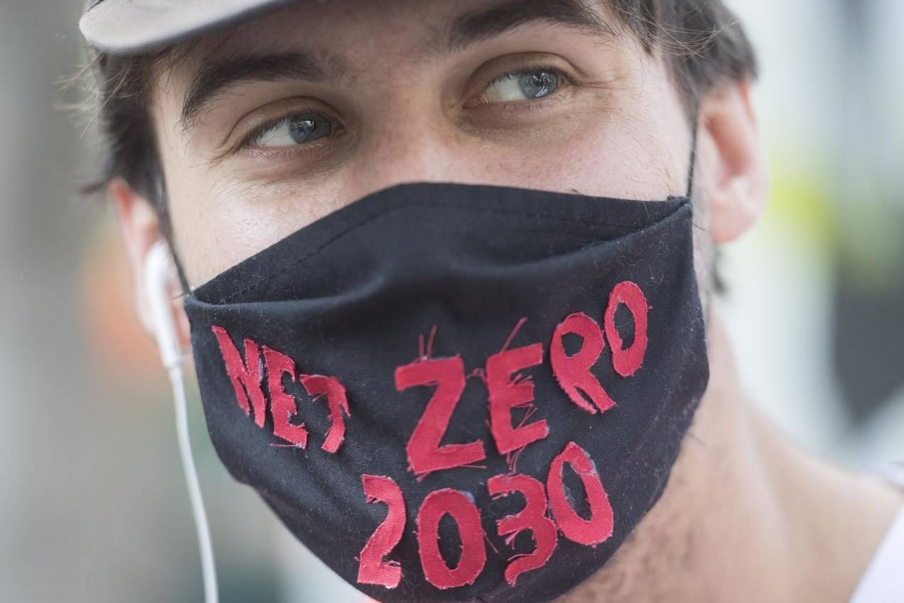 A man attends a climate change protest in Montreal on Saturday, Sept. 26, 2020. A report by the Canadian Institute for Climate Choices says climate change will add more than $100 billion to Canada's health-care costs by mid-century. THE CANADIAN PRESS/Graham Hughes
