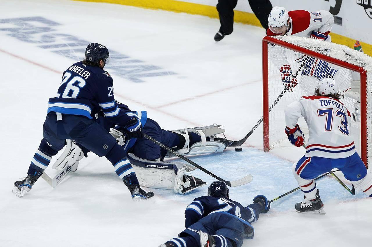 Montreal Canadiens' Nick Suzuki (14) scores on Winnipeg Jets goaltender Connor Hellebuyck (37) as Blake Wheeler (26) and Derek Forbort (24) defend during first-period NHL Stanley Cup playoff hockey action in Winnipeg, Wednesday, June 2, 2021. THE CANADIAN PRESS/John Woods