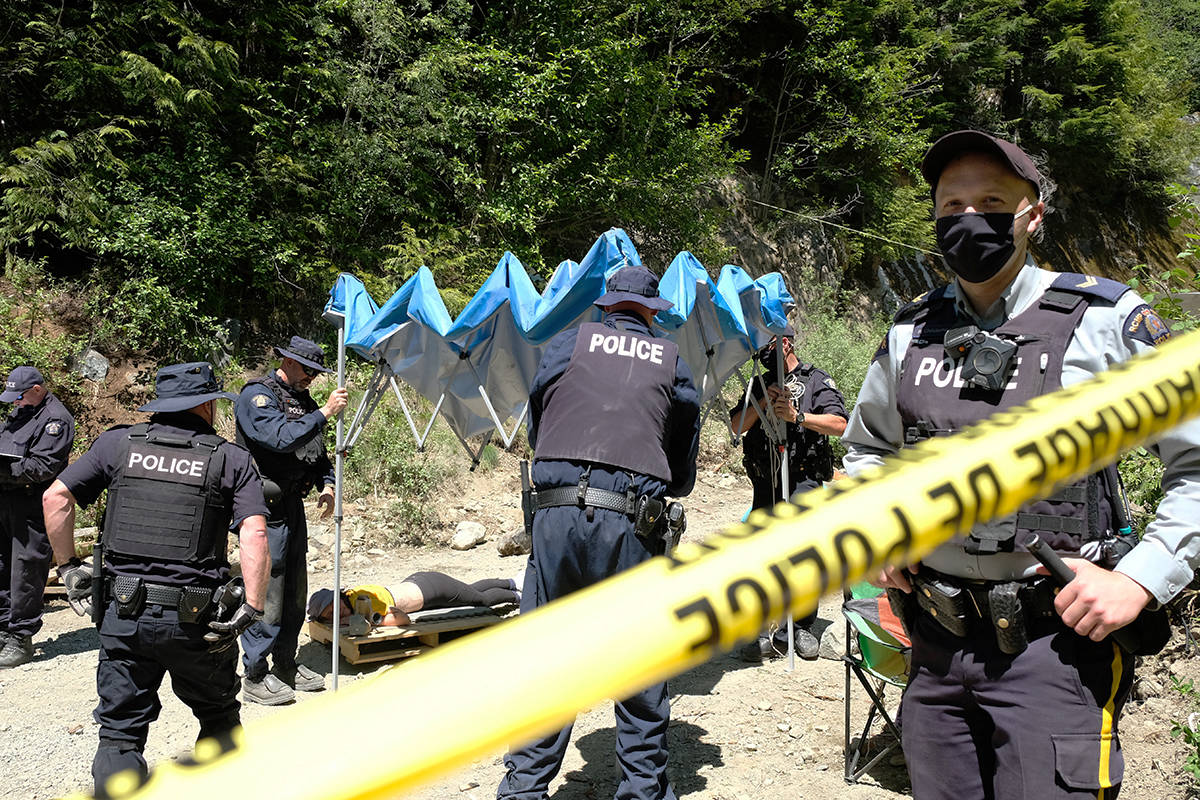 """Police take down a tent they'd set up as they prepared to leave the Waterfall blockade. A protester, Kat Ellis, lays on the ground still locked into the """"sleeping dragon."""" She unlocked herself as police drove away. (Zoe Ducklow/News Staff)"""