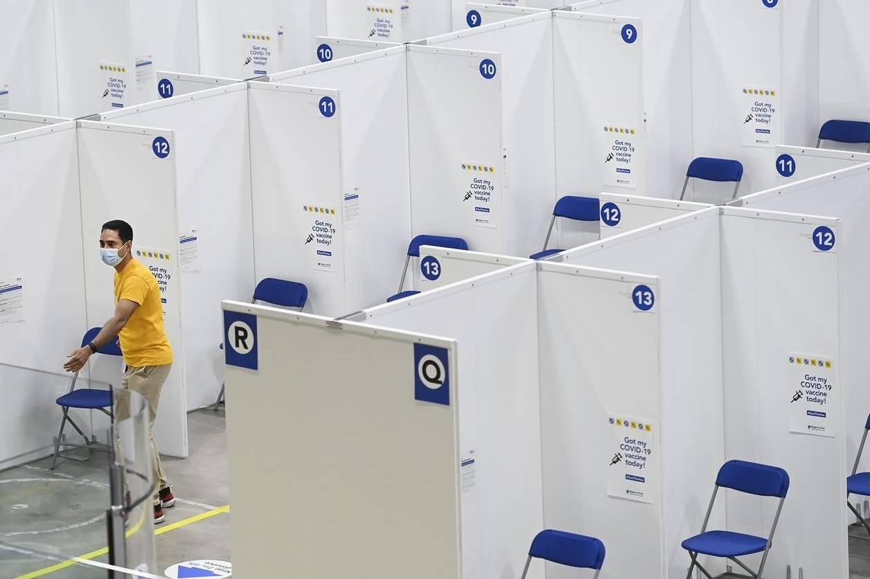 """A man walks through rows of chairs and privacy cubicles at the """"Hockey Hub"""" mass vaccination centre, known as the CAA Centre, during the COVID-19 pandemic in Brampton, Ont., on Thursday, June 3, 2021. This NHL-sized hockey rink is one of Canada's largest vaccination centres. THE CANADIAN PRESS/Nathan Denette"""