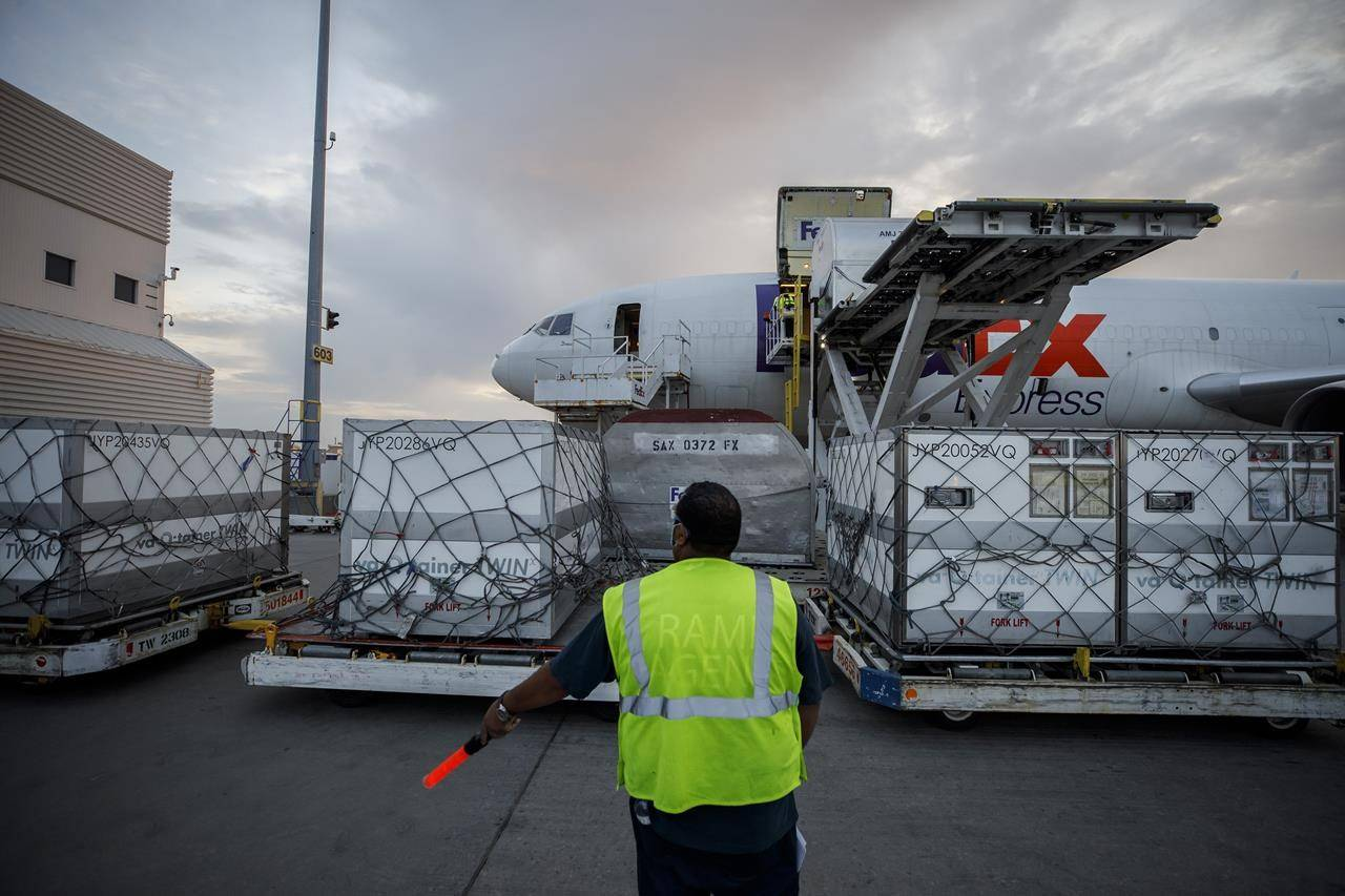 Workers unload a shipment of the Moderna COVID‑19 vaccine at the FedEx hub at Pearson International Airport in Toronto on Thursday, May 20, 2021. Procurement Minister Anita Anand says Canada is trying to negotiate a deal to start getting doses of Moderna's COVID-19 vaccine from the United States instead of Europe. THE CANADIAN PRESS/Cole Burston