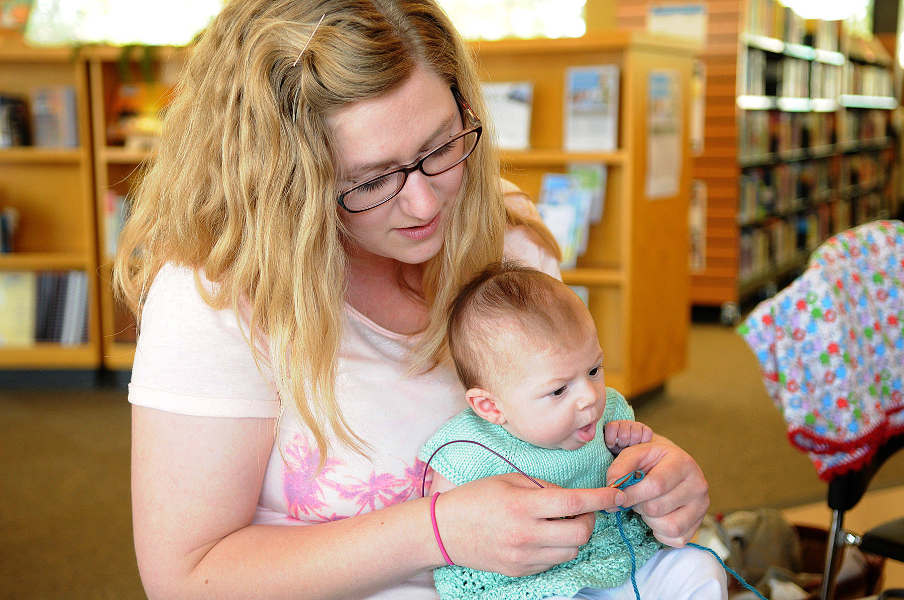 Karen Page knits at the Sardis Library while holding her daughter Rosalie during Worldwide Knit in Public Day on June 17, 2015 in Chilliwack. Saturday, June 12, 2021 is Worldwide Knit in Public Day. (Jenna Hauck/ Chilliwack Progress file)