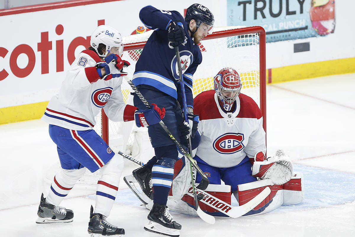 Montreal Canadiens goaltender Carey Price (31) saves the tip from Winnipeg Jets' Pierre-Luc Dubois (13) as Ben Chiarot (8) defends during first period NHL playoff action in Winnipeg on Friday, June 4, 2021. THE CANADIAN PRESS/John Woods