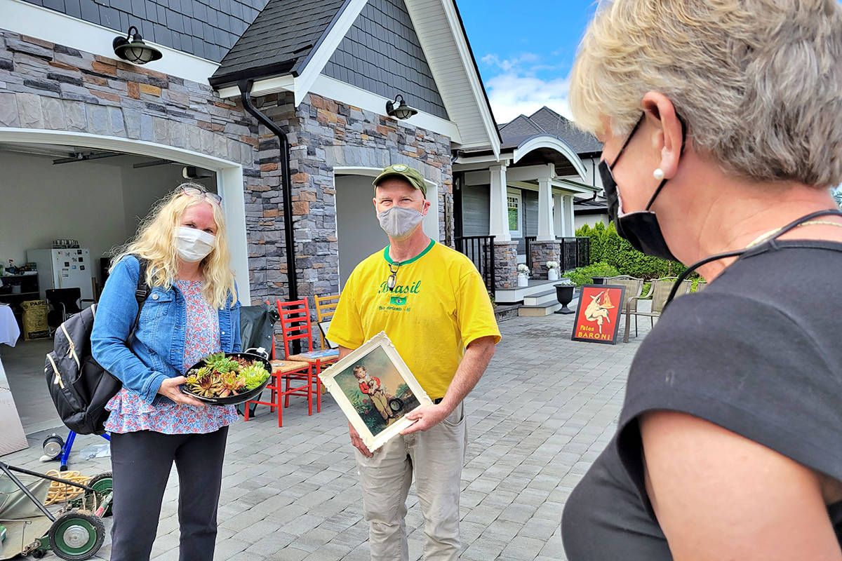 Darcy and Karen Bonneteau dropped by Kim McDougall's house in Murrayville Saturday for the community garage sale that organizers described as 'crazy busy' (Dan Ferguson/Langkey Advance Times)