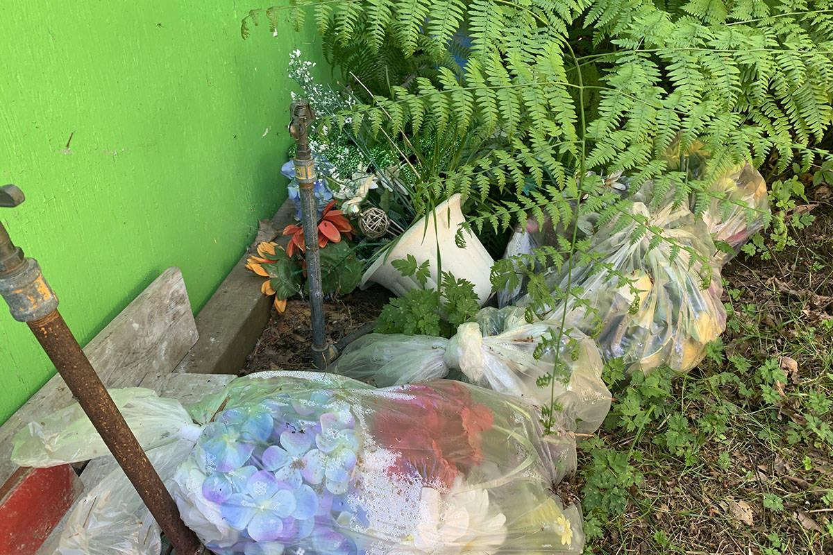 Flowers and other adornments left at Hope Cemetery have been moved off to a back storage and maintenance area. Some are bagged and now collecting condensation and insects inside. (Jessica Peters/ Hope Standard)