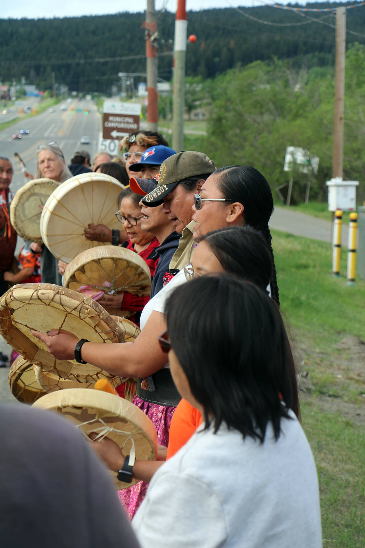 Around a dozen of those who gathered to honour the convoy brought drums and sang as the trucks passed. (Patrick Davies photo - 100 Mile Free Press)