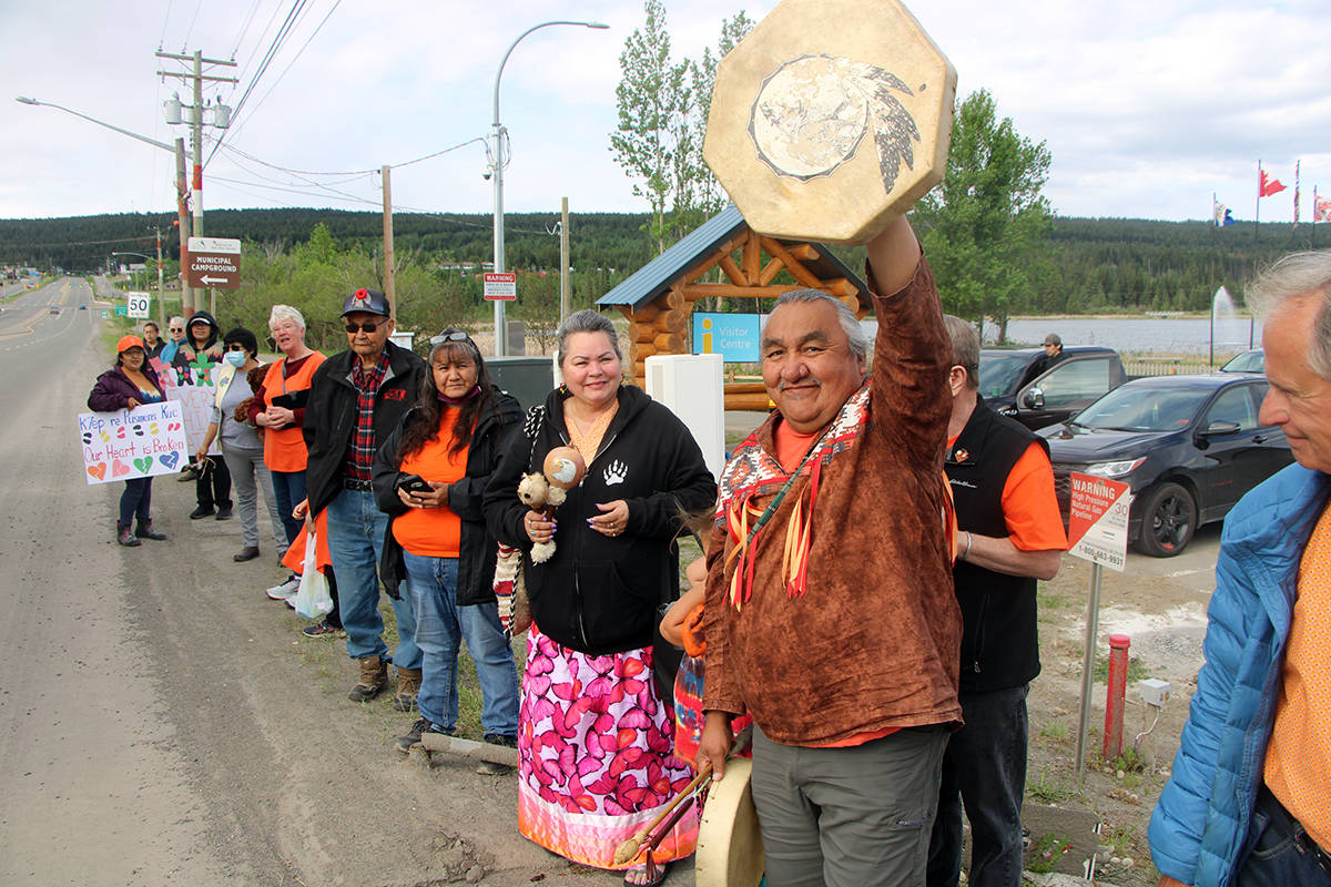 Former Canim Lake Band chief Mike Archie raises his drum in salute as car and trucks honk at the gathered community members of the Canim Lake Band and 100 Mile House. (Patrick Davies photo - 100 Mile Free Press)