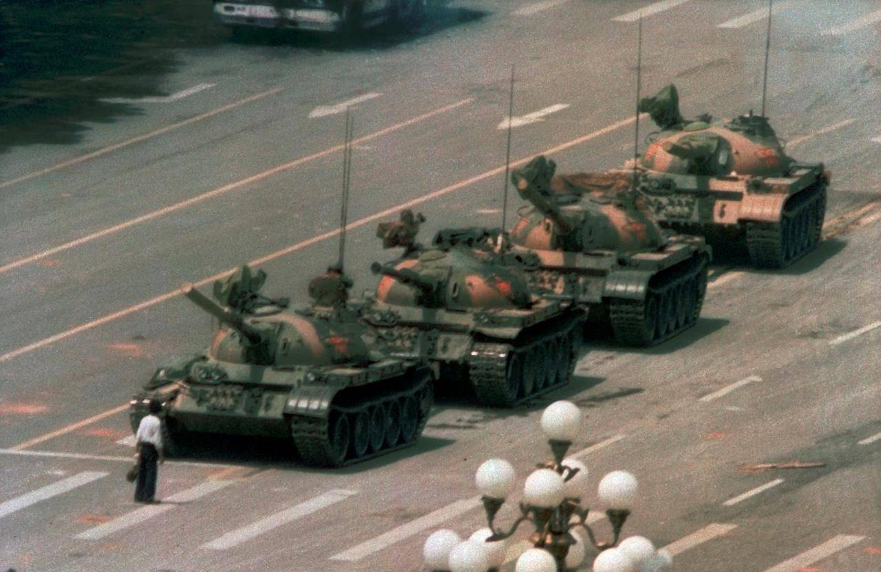 """In this June 5, 1989 file photo, a man stands alone to block a line of tanks heading east on Beijing's Cangan Blvd. in Tiananmen Square."""" (AP Photo/Jeff Widener)"""