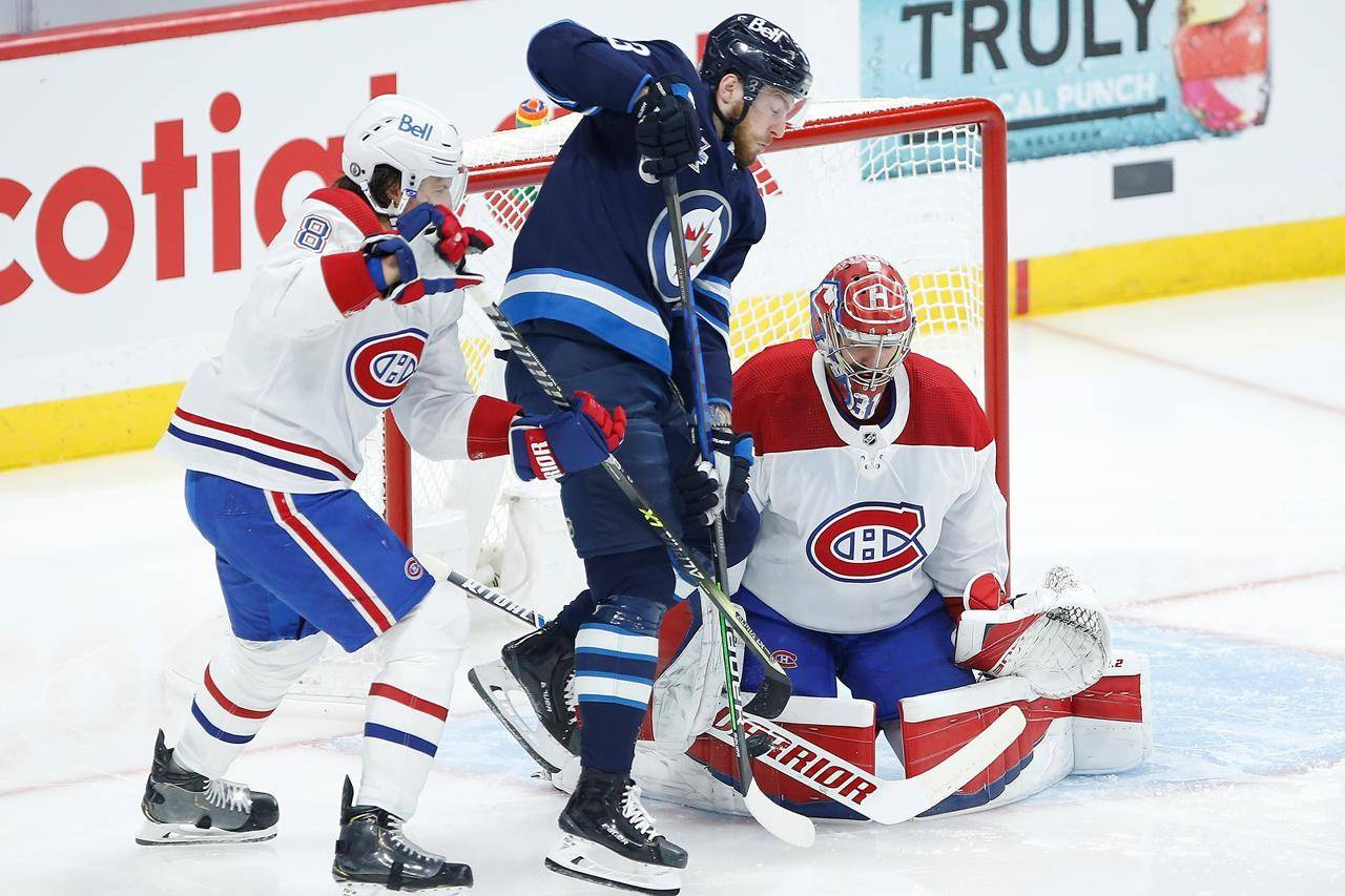 Montreal Canadiens goaltender Carey Price (31) saves the tip from Winnipeg Jets' Pierre-Luc Dubois (13) as Ben Chiarot (8) defends during first period NHL playoff action in Winnipeg on June 4, 2021. THE CANADIAN PRESS/John Woods