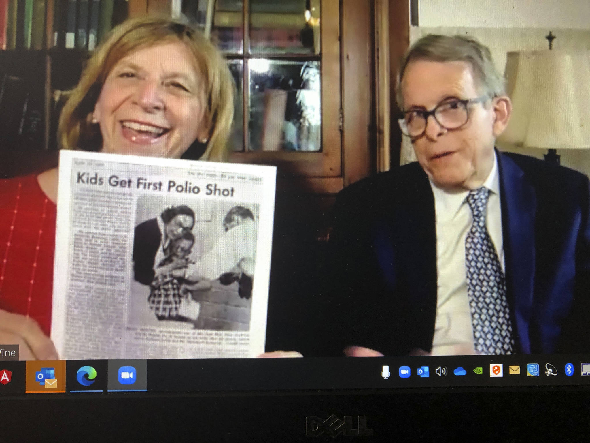 This photograph of a computer screen during a virtual interview on April 9, 2021, shows Ohio Gov. Mike DeWine, right, as he sits with his wife Fran DeWine while she holds a printed copy of the Yellow Springs News issue page from April 28, 1955 that shows DeWine as a then second-grader, while receiving his polio vaccination. Tens of millions of today's older Americans lived through the polio epidemic, their childhood summers dominated by concern about the virus. Some parents banned their kids from public swimming pools and neighborhood playgrounds and avoided large gatherings. Some of those from the polio era are sharing their memories with today's youngsters as a lesson of hope for the battle against COVID-19. Soon after polio vaccines became widely available, U.S. cases and death tolls plummeted to hundreds a year, then dozens in the 1960s, and to U.S. eradication in 1979.(AP Photo/Dan Sewell)