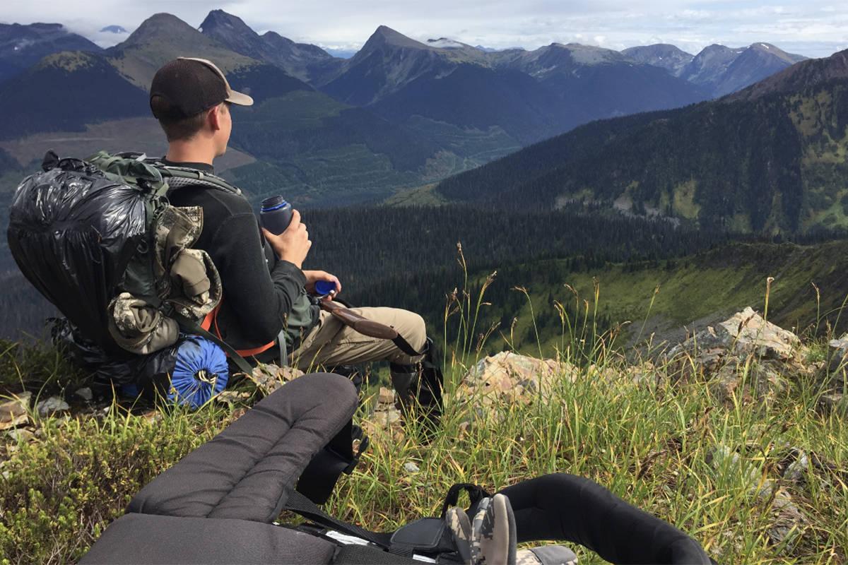 Sam Fait takes a break to enjoy the view from the mountains east of Williams Lake. (Williams Lake Tribune photo)