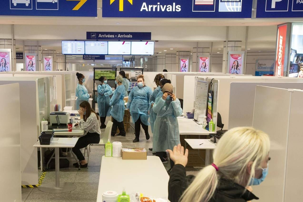 Health-care workers wait for airline passengers at a COVID-19 testing centre at Trudeau Airport in Montreal, Friday, Feb. 19, 2021. THE CANADIAN PRESS/Ryan Remiorz