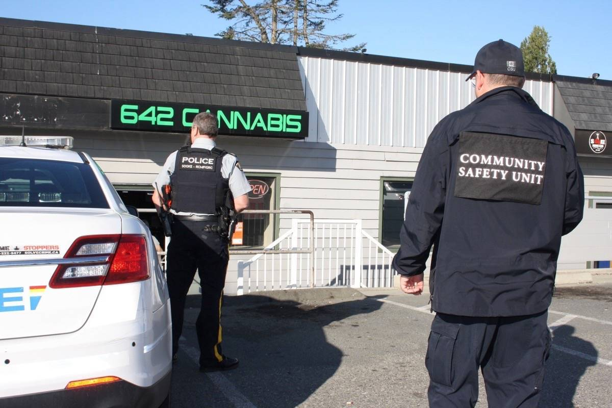 """B.C.'s """"community safety unit"""" and police raid an unlicensed cannabis store in Sooke, Oct. 27, 2019. (Tim Collins/Sooke News Mirror)"""