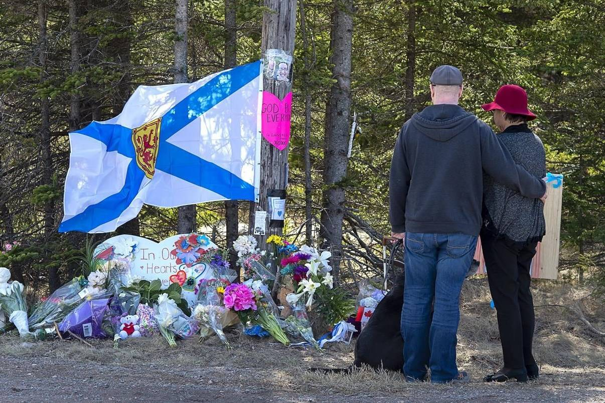 A couple pays their respects at a roadblock in Portapique, N.S. on Wednesday, April 22, 2021. Public hearings are scheduled to begin in October for the public inquiry into the 2020 Nova Scotia mass shooting. THE CANADIAN PRESS/Andrew Vaughan