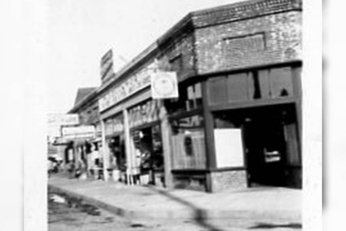 """Former BC Liquor Control Board employee Ron Hyde helped oversee construction of stores around the province, says Langley Heritage Society who received this photo from Hyde. He says, """"The second Langley Prairie store operated from this (above) location from 1933 – 1941. The liquor store is in the slanted corner of the building with some great views of businesses along the street with store signs etc. The liquor store windows have curtains on them which was a requirement by the B.C. Liquor Control Board on all their stores — this was to ensure that young people could not see into the store and see the bottles of alcohol on the shelves."""" (Langley Heritage Society)"""