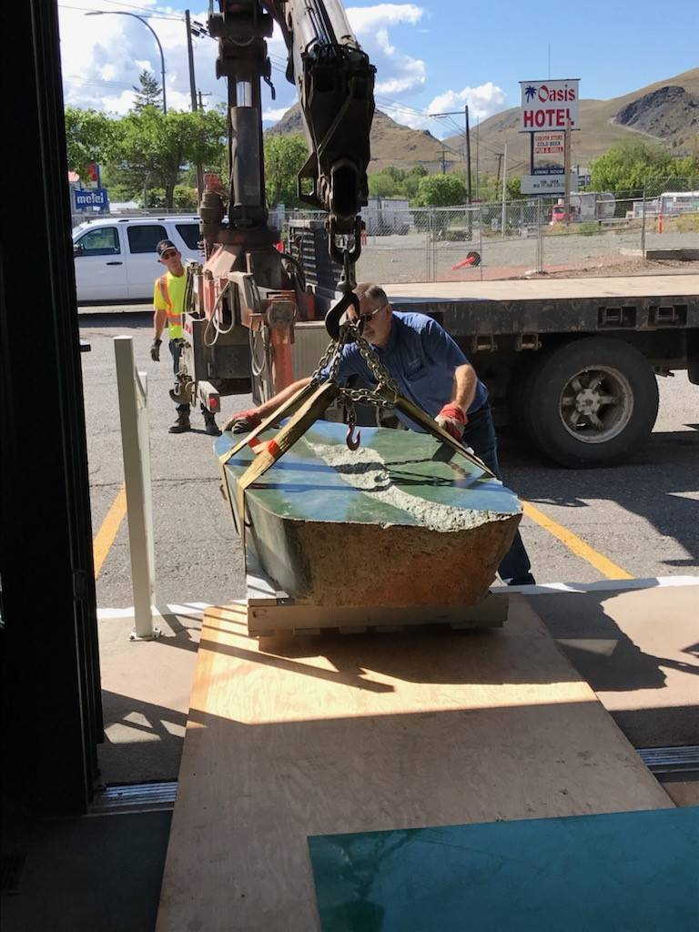 Andy Anderson of Ashcroft Home Hardware (rear) and Bill Elliott manoeuvre the jade boulder up the steps into the Cariboo Jade Shop, June 2021. (Photo credit: Heidi Roy)