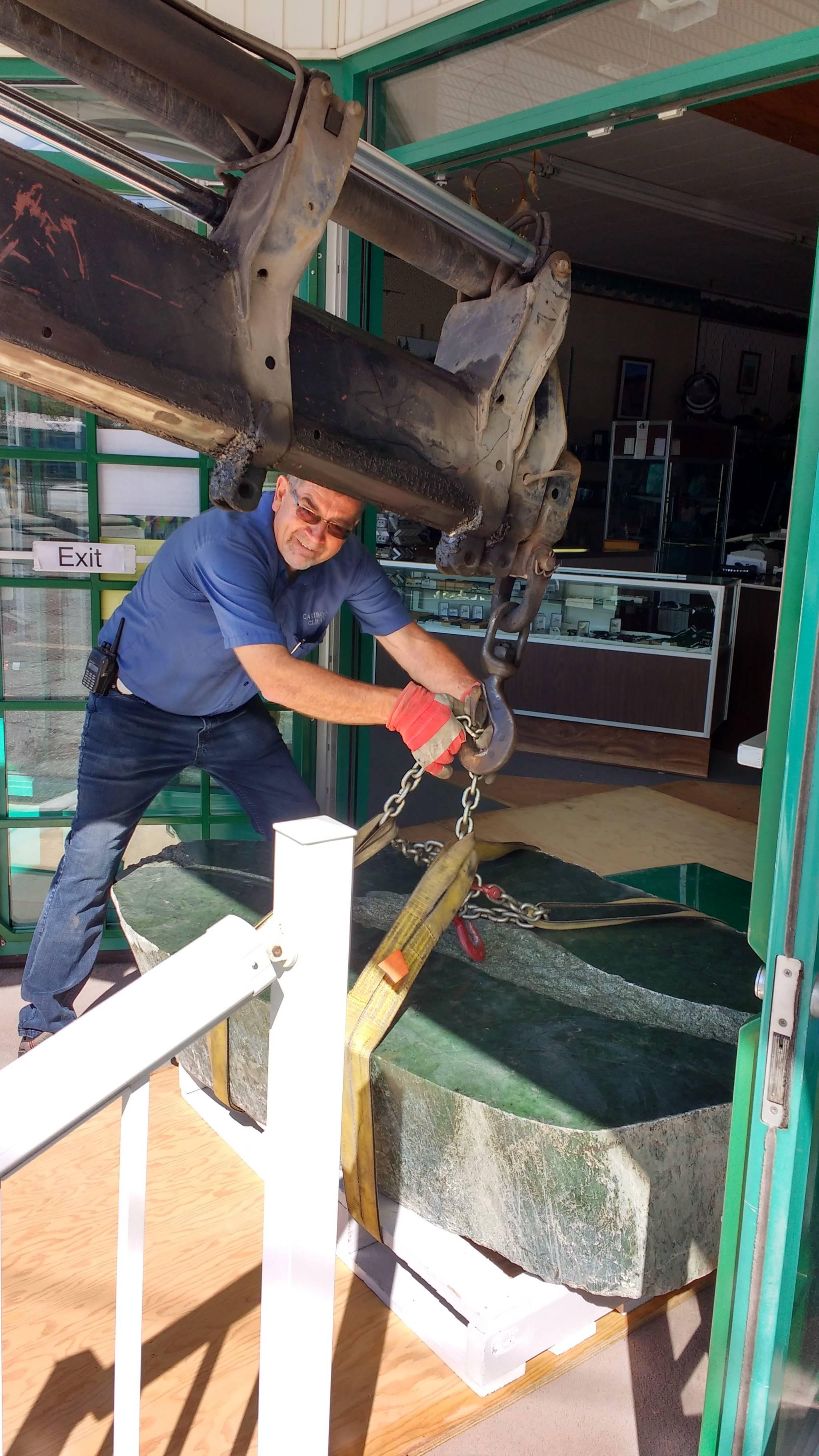 Bill Elliott manoeuvres the jade boulder into the shop. (Photo credit: Heidi Roy)