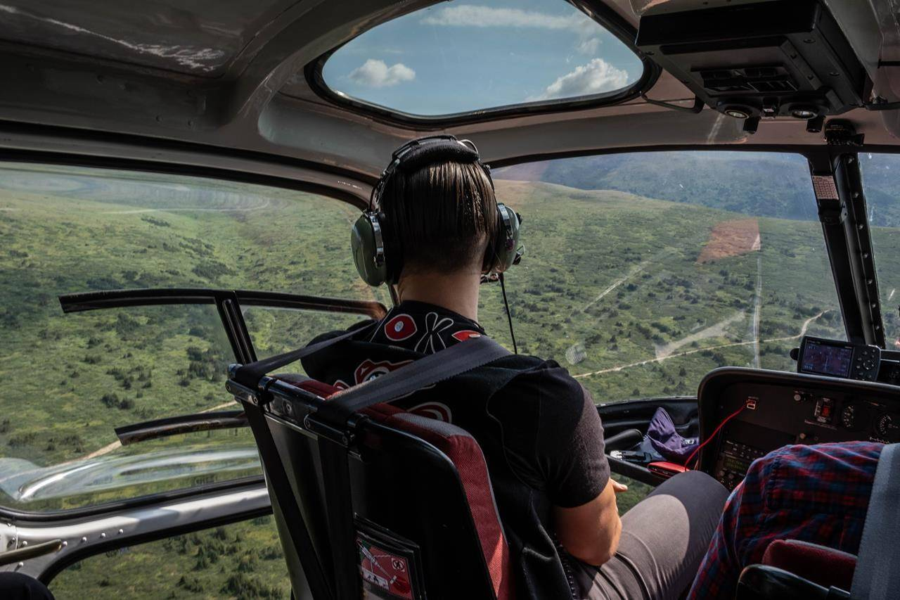 """President of the Tahltan Central Government, Chad Norman Day, surveys Tahltan territory by helicopter in this July 2019 handout photo. The Tahltan Nation and the British Columbia government have struck what officials say is a historic agreement for shared decision-making for the nation's territory in northwestern B.C., a hot spot for mineral exploration. Day says the deal shows they are """"getting closer and closer to a true nation-to-nation relationship."""" THE CANADIAN PRESS/HO - Tahltan Central Government"""