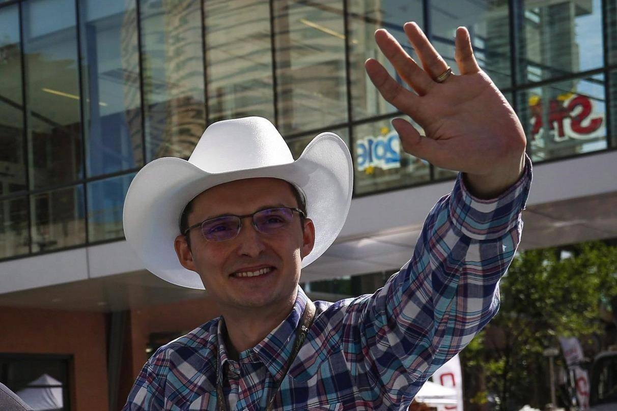 Conservative MP Tom Kmiec waves to the crowd during the Calgary Stampede parade in Calgary, Friday, July 8, 2016. THE CANADIAN PRESS/Jeff McIntosh