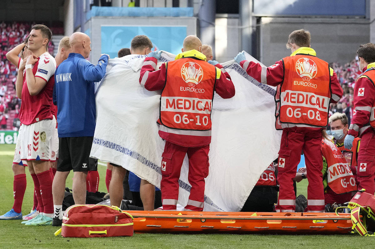 Denmark's Christian Eriksen receives medical attention after collapsing during the Euro 2020 soccer championship group B match between Denmark and Finland at Parken stadium in Copenhagen, Saturday, June 12, 2021. (AP Photo/Martin Meissner, Pool)