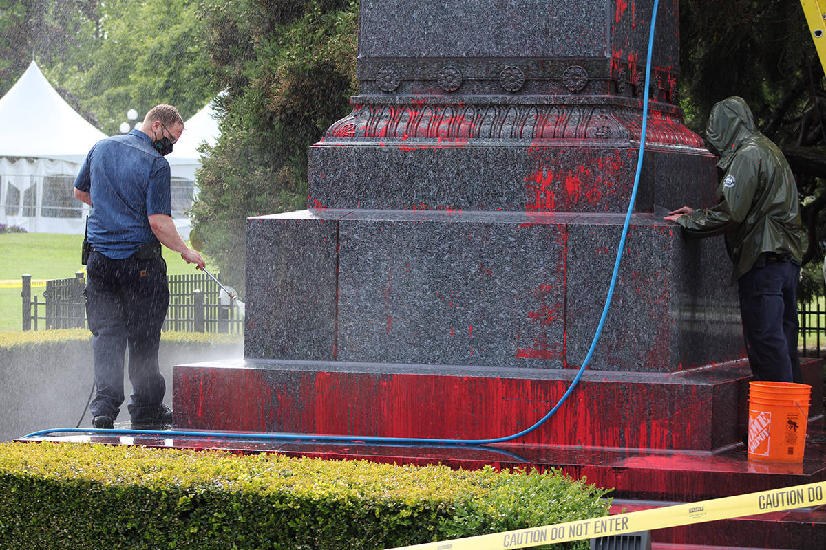 Workers clean off the red paint sprayed on the statue of Queen Victoria at the front of the B.C. legislature Friday. (Jake Romphf/News Staff)