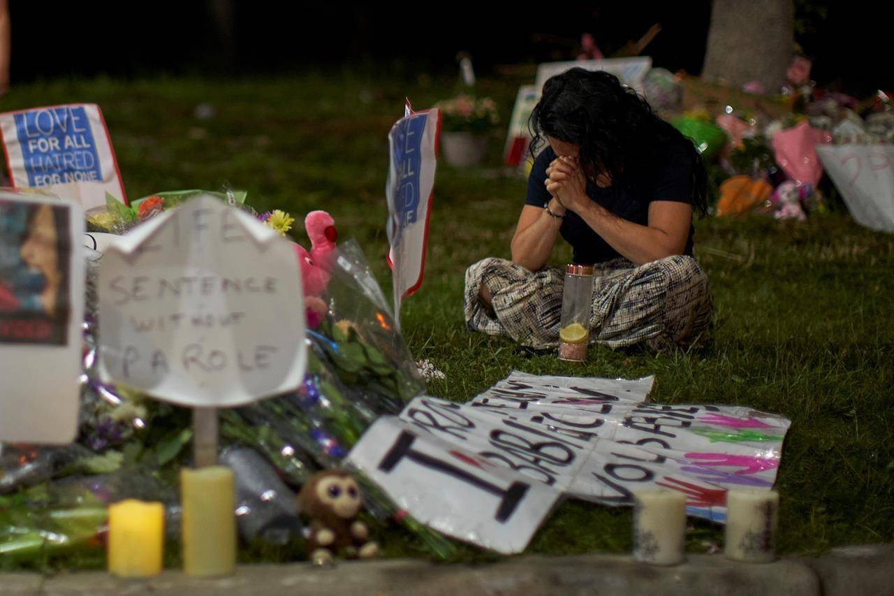 A woman sits and weeps at the scene of Sunday's hate-motivated vehicle attack in London, Ont. on Tuesday, June 8, 2021. THE CANADIAN PRESS/ Geoff Robins