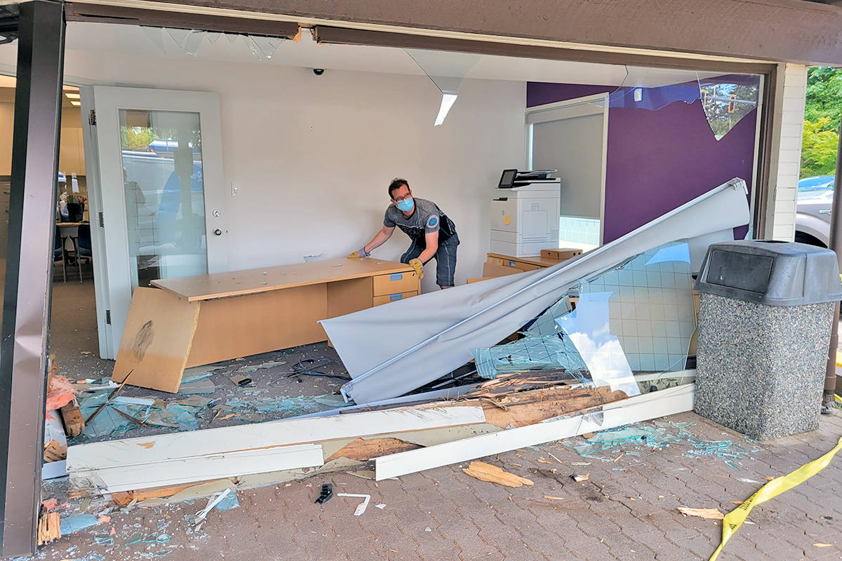 A worker clears out damaged fixtures from a front office of Coast Capital Savings credit union in Brookswood 4145 - 200th Street on Saturday, June 12, after a car knocked out an exterior roof support beam and smashed in a window. (Dan Ferguson/Langley Advance Times)