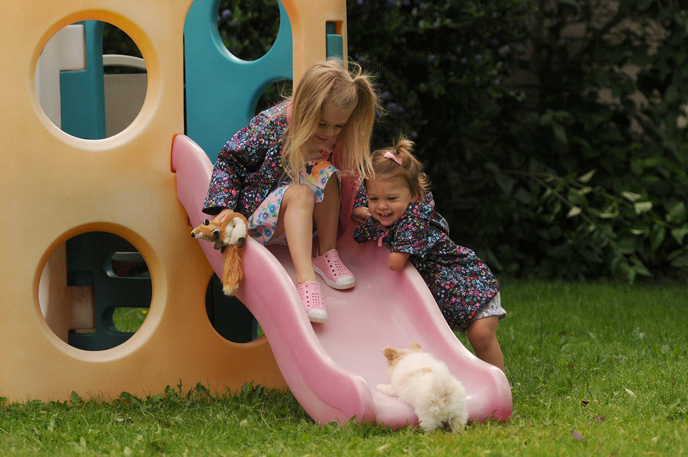 Two-year-old Ivy McLeod and five-year-old sister Elena play with Lucky the puppy outside their Chilliwack home on Thursday, June 10, 2021. (Jenna Hauck/ Chilliwack Progress)