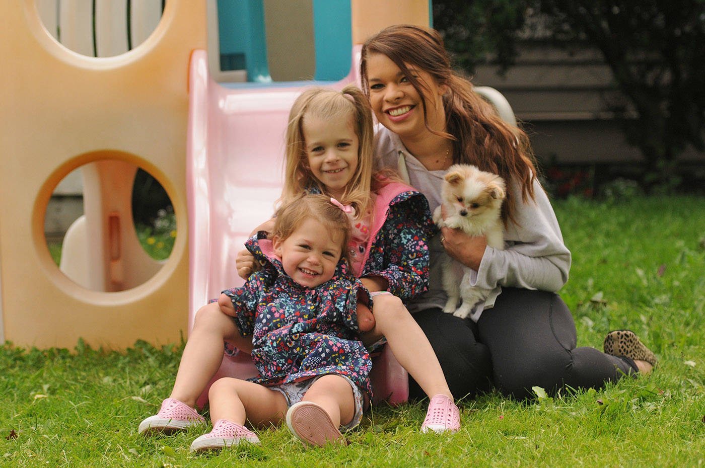 The McLeod family – Ivy, 2, Elena, 5, and mom Vanessa – are seen with their new puppy Lucky outside their home in Chilliwack on Thursday, June 10, 2021. Not pictured is husband/dad Sean McLeod. (Jenna Hauck/ Chilliwack Progress)