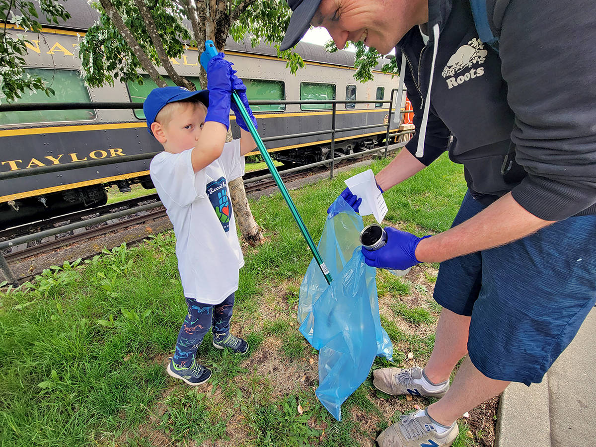William Bush, 5, used a pickup tool to drop trash into a bag held by his dad, Jon during a community cleanup event in Fort Langley on Saturday, June 12. (Dan Ferguson/Langley Advance Times)