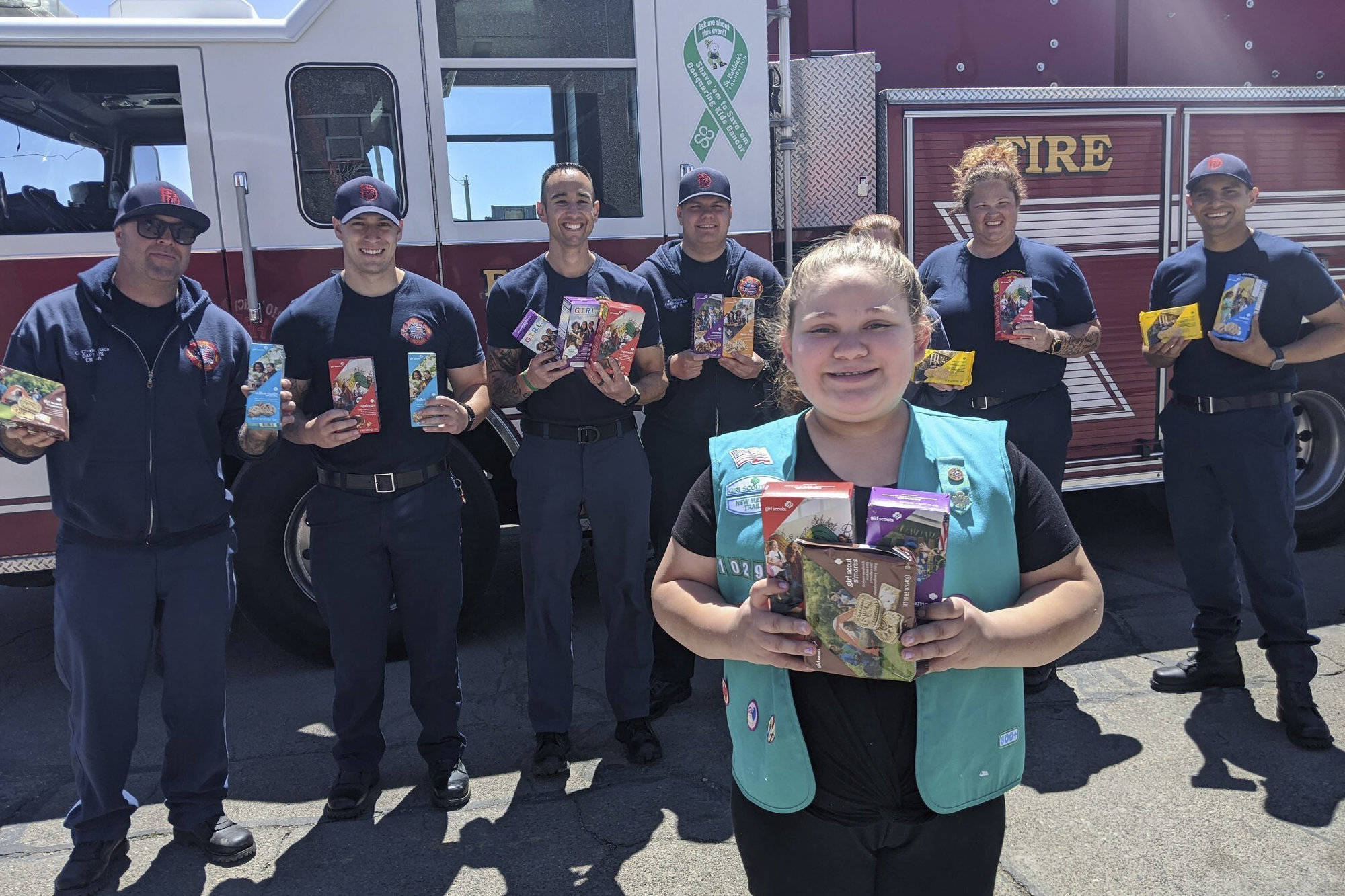 This undated photo provided by Girl Scouts of New Mexico Trails shows a scout donating cookies to firefighters in Rio Rancho, New Mexico, as part of the Hometown Heroes program. As the coronavirus pandemic wore into the spring selling season, many Girl Scout troops nixed their traditional cookie booths for safety reasons. That resulted in millions of boxes of unsold cookies. (Girl Scouts of New Mexico Trails via AP)