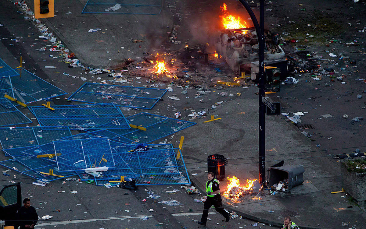 A police officer runs past debris and fires after rioters burned police cars after the Vancouver Canucks were defeated by the Boston Bruins in the NHL's Stanley Cup Final in Vancouver, B.C., on Wednesday June 15, 2011. THE CANADIAN PRESS/Darryl Dyck