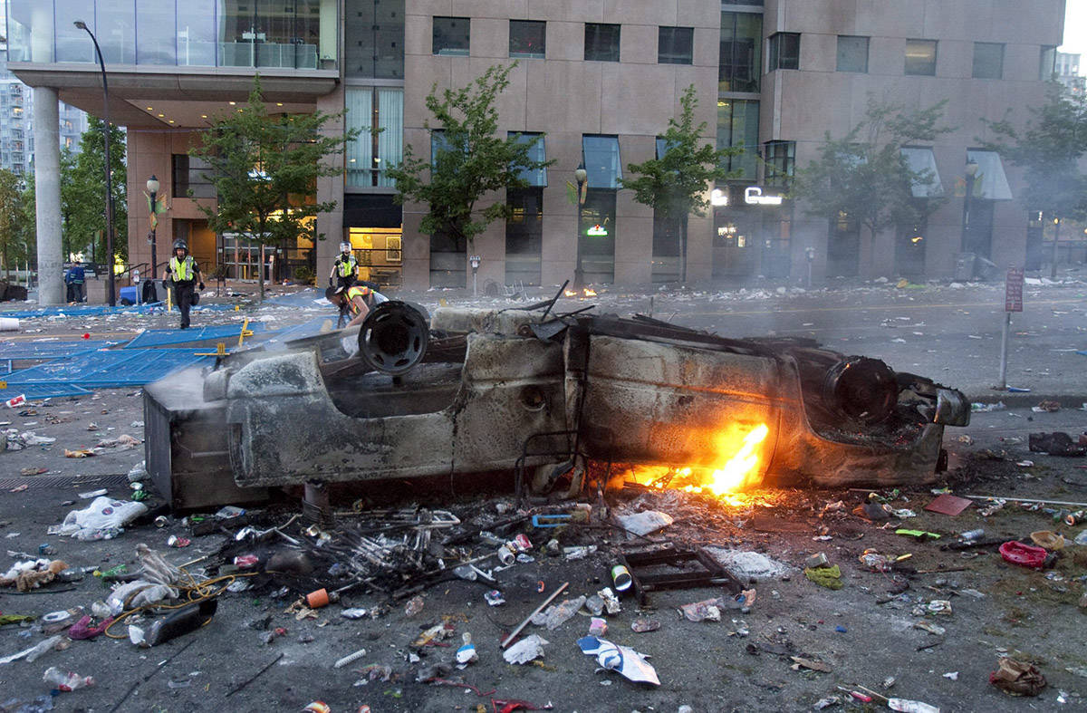 A burnt out car lies upside down in the street during a riot in downtown Vancouver, Wednesday, June 15, 2011 following the Vancouver Canucks 4-0 loss to the Boston Bruins in game 7 of the Stanley Cup hockey final. THE CANADIAN PRESS/Geoff Howe