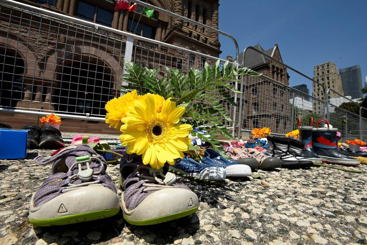 Children's shoes and flowers are shown after being placed outside the Ontario legislature in Toronto on Monday, May 31, 2021. THE CANADIAN PRESS/Frank Gunn