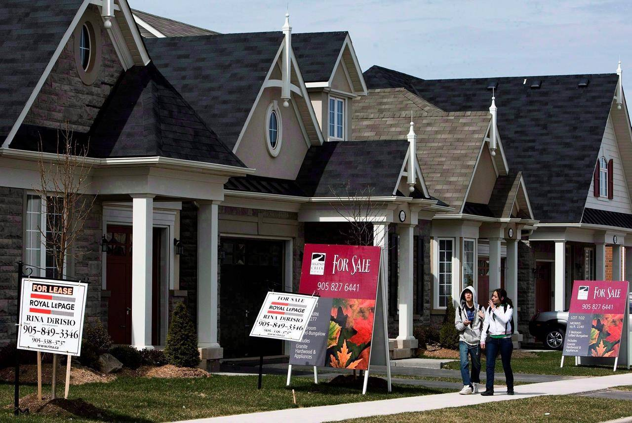 People walk past new homes for sale in Oakville, Ont., on Tuesday, April 14, 2009. THE CANADIAN PRESS/Nathan Denette