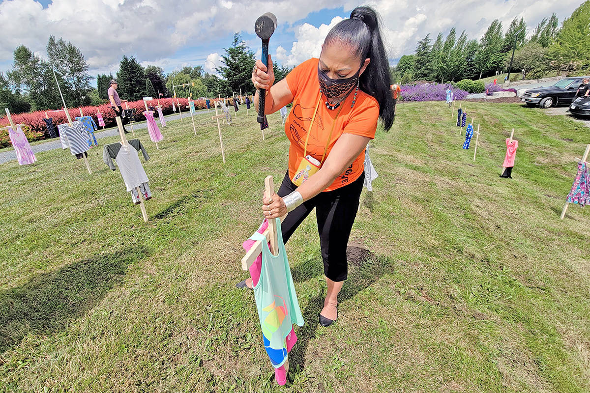 Una-Ann Moyer was one of several volunteers who installed 215 crosses bedecked with children's clothes in memory of the Kamloops residential school victims at the Derek Doubleday Arboretum at 21559 Fraser Hwy. Langley on Tuesday, June 15. (Dan Ferguson/Langley Advance Times)