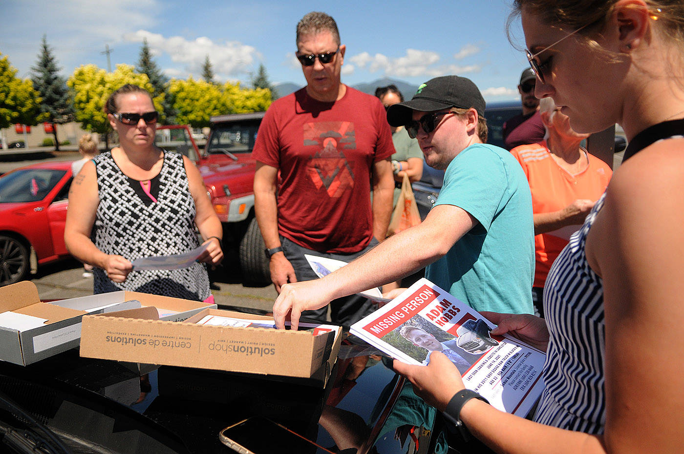 Brandon Hobbs (turquoise shirt), brother of missing Abbotsford man Adam Hobbs, gathers with other family and friends to distribute posters in Chilliwack on Thursday, June 17, 2021. (Jenna Hauck/ Chilliwack Progress)