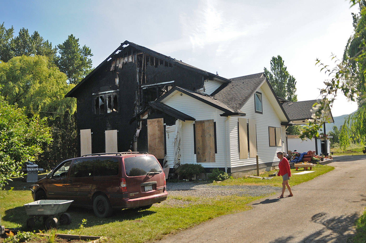 A tenant walks in front of her home on Boundary Road on Friday, June 18, 2021 after it was destroyed by fire the night before in Chilliwack. (Jenna Hauck/ Chilliwack Progress)