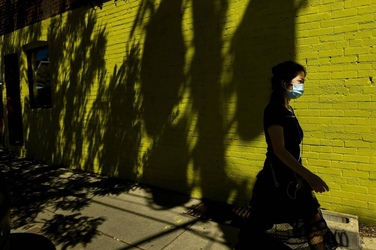 A person walks past a colourful wall while wearing a protective mask in the warm weather during the COVID-19 pandemic in Toronto on Wednesday, June 16, 2021. THE CANADIAN PRESS/Nathan Denette