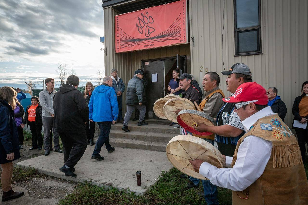 British Columbia Premier John Horgan, centre, wearing a blue jacket, is drummed into the Lower Post Residential School by Kaska drummers in Lower Post, B.C., on Orange Shirt Day in a 2019 handout photo. A ceremony to mark the demolition of a former residential school building in a remote British Columbia community has been postponed following the discovery of remains by construction workers that turned out to be those of an animal. THE CANADIAN PRESS/HO-Manu Keggenhoff MANDATORY CREDIT