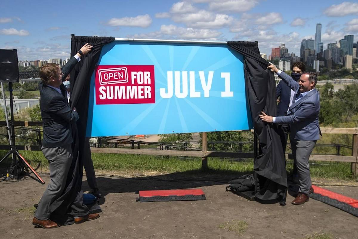 Albert Health Minister Tyler Shandro and Alberta Premier Jason Kenney unveil an opening sign after speaking about the Open for Summer Plan and next steps in the COVID-19 vaccine rollout, in Edmonton, Friday, June 18, 2021. THE CANADIAN PRESS/Jason Franson