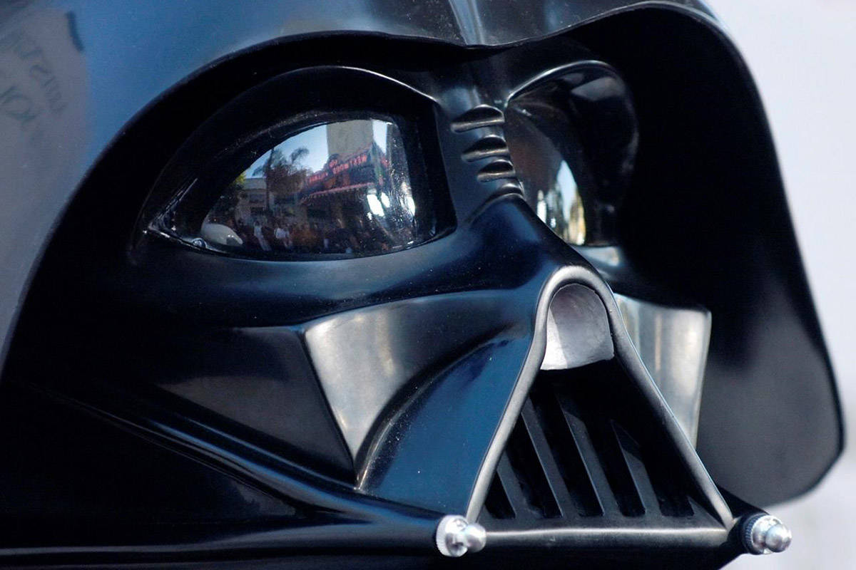 """In this file photo dated Thursday, May 12, 2005, the Los Angeles, premiere of the movie """"Star Wars: Revenge of the Sith"""", is reflected in the mask eyeglasses of iconic baddie character Darth Vader. In the movie franchise, who was Darth Vader's son? (AP Photo/Chris Pizzello, FILE)"""