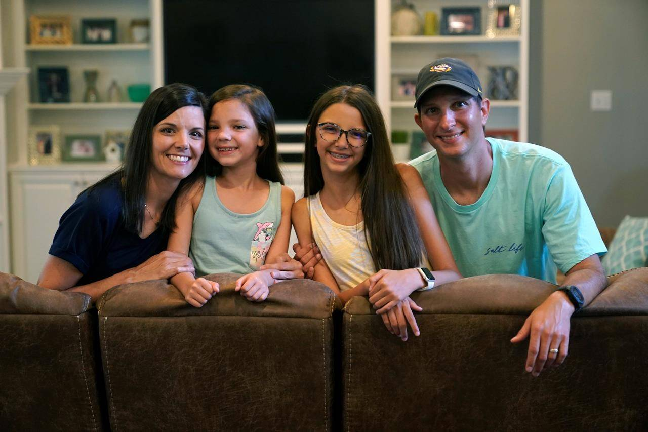 Cecilia Shaffette, second from right, poses for a family portrait with her father Rhett, sister Lydia and mother Angelle in their home in Carriere, Miss., Wednesday, June 16, 2021. (AP Photo/Gerald Herbert)