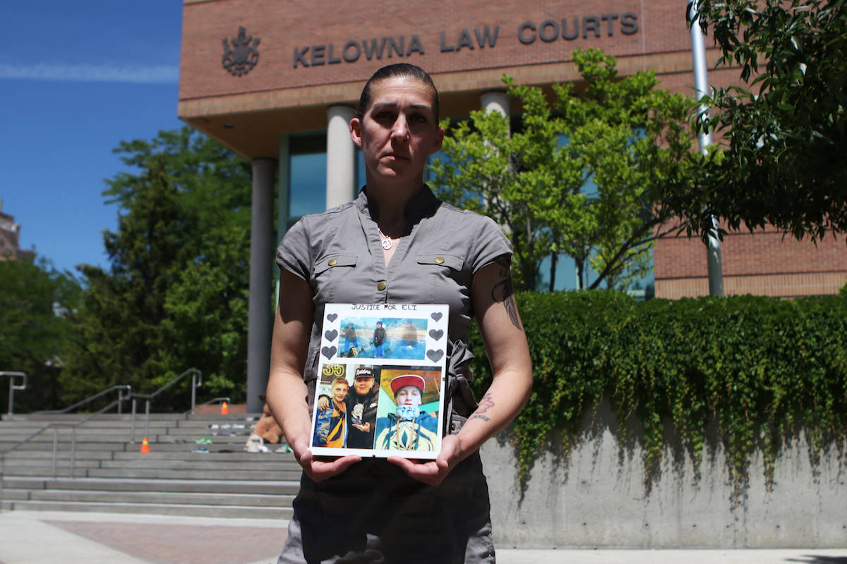 Emily Steele holds up a collage of her son, 16-year-old Elijah-Iain Beauregard who was stabbed and killed in June 2019, outside of Kelowna Law Courts on June 18. (Aaron Hemens/Capital News)