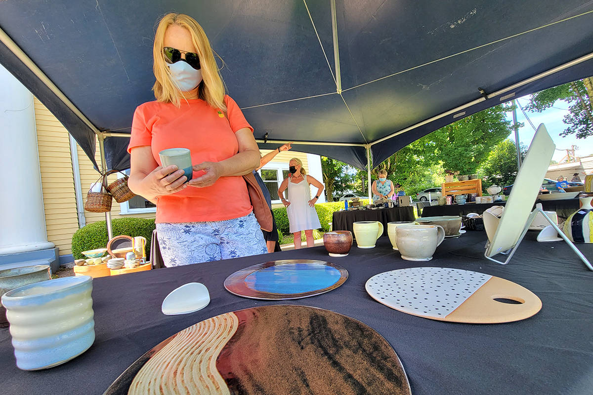 A visitor looks over some of the works by a member of the Fraser Valley Potters Guild, at the Sunday, June 20 Hearts For Hospice event at the Fort Langley Community Hall. (Dan Ferguson/Langley Advance Times)