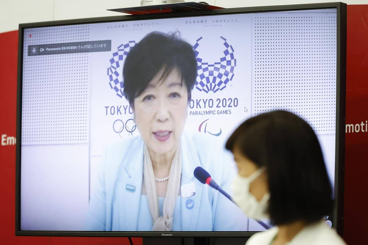 Tokyo Gov. Yuriko Koike, on a screen, speaks as Japanese Olympic Minister Tamayo Marukawa listens during a five-party online meeting at Harumi Island Triton Square Tower Y in Tokyo Monday, June 21, 2021. The Tokyo Olympics will allow some local fans to attend when the games open in just over a month, Tokyo organizing committee officials and the IOC said on Monday. Organizers set a limit of 50% of capacity up to a maximum of 10,000 fans for all Olympic venues. (Rodrigo Reyes Marin/Pool Photo via AP)