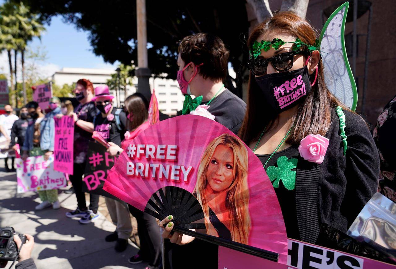 FILE - Britney Spears supporter Kiki Norberto holds a hand fan outside a court hearing concerning the pop singer's conservatorship on March 17, 2021, in Los Angeles. When Spears speaks to a judge at her own request on Wednesday, June. 23, 2021, she'll do it 13 years into a court-enforced conservatorship that has exercised vast control of her life and money by her father. Spears has said the conservatorship saved her from collapse and exploitation. But she has sought more control over how it operates, and says she wants her father out. (AP Photo/Chris Pizzello, File)