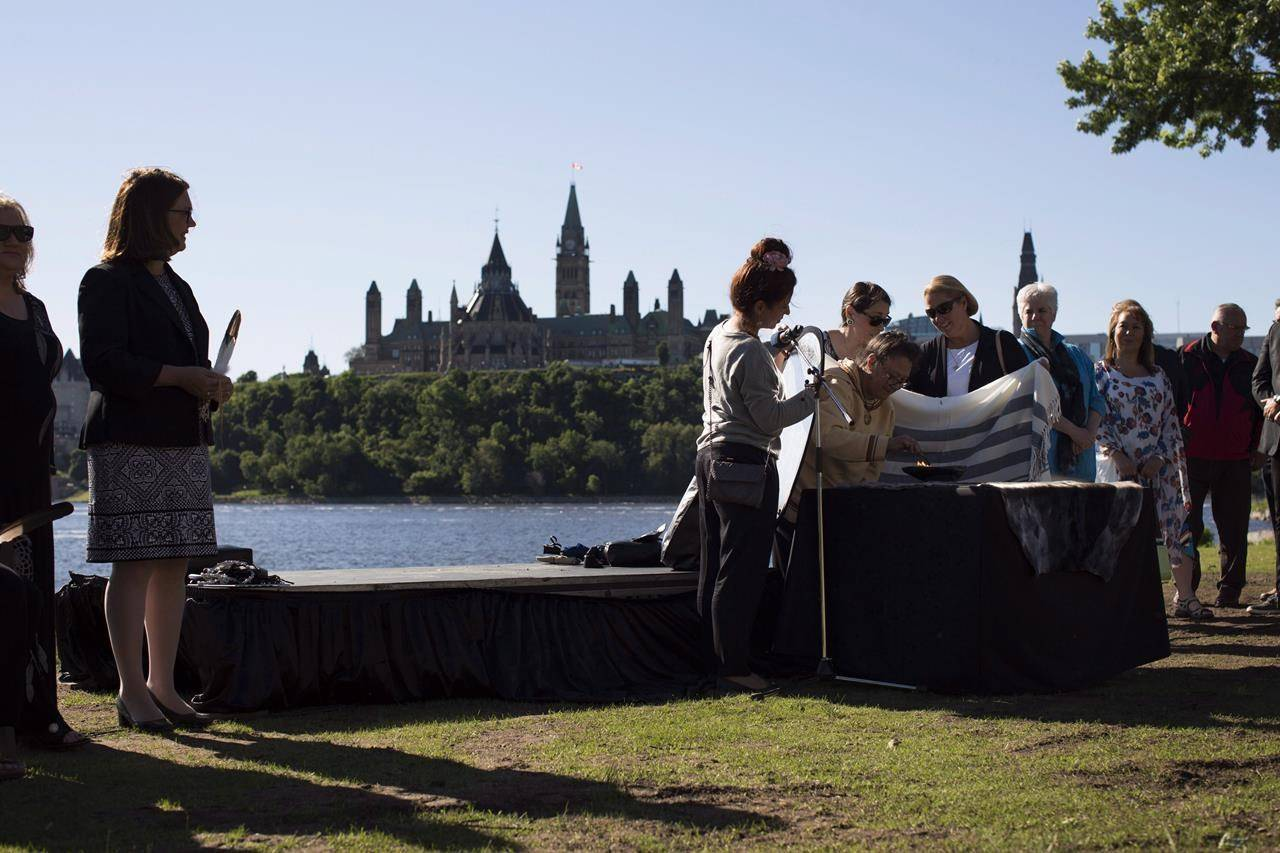 Inuk elder Reepa Evic-Carleton light a qulliq, a traditional oil lamp, at a public ceremony to celebrate National Indigenous Peoples Day on the bank of the Ottawa River behind the Canadian Museum of History in Gatineau, Que. on Thursday, June 21, 2018. THE CANADIAN PRESS/David Kawai