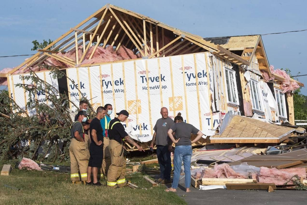 People look over the damage after a tornado touched down in Mascouche, Que., north of Montreal, Monday, June 21, 2021. Dozens of homes were damaged and one death has been confirmed. THE CANADIAN PRESS/Ryan Remiorz