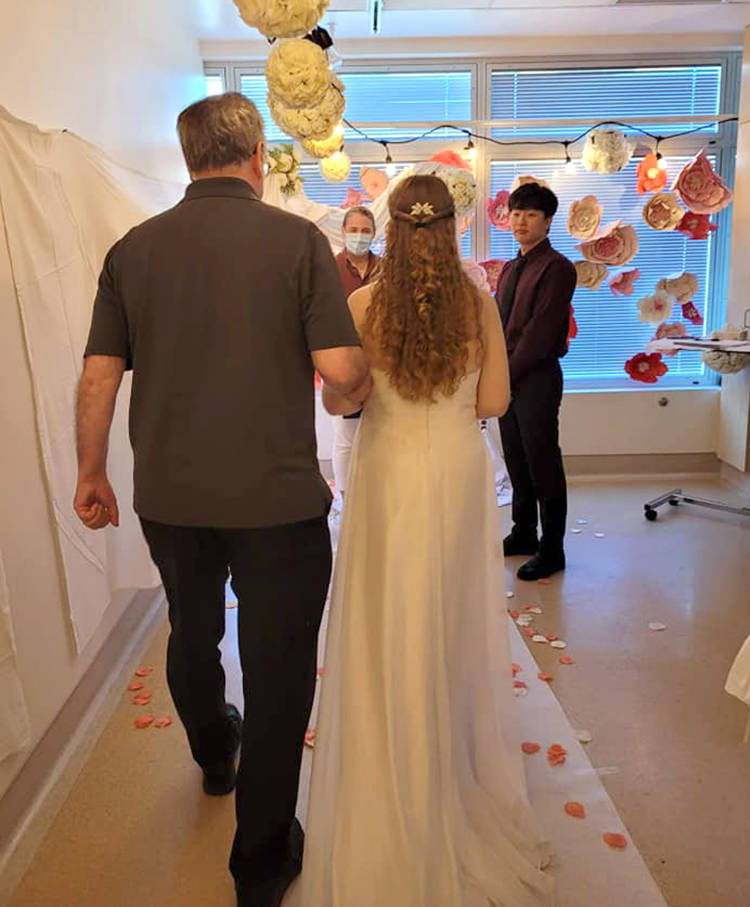 Robin Sanford is walked down the aisle by her dad Robert as fiance Simon Park waits during their wedding at Abbotsford Regional Hospital on June 16. (Submitted photo)